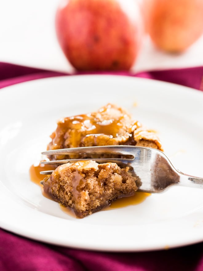 A fork digging into a slice of apple cake.