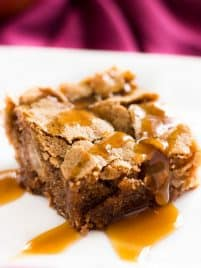 Slice of caramel apple cake on a plate with homemade caramel sauce drizzle