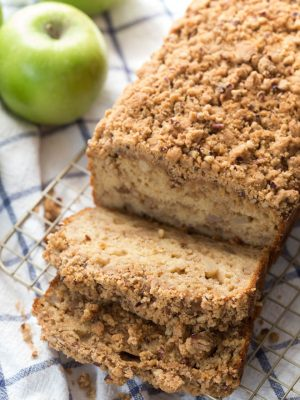 Greek Yogurt Apple Spice Bread is lightened up with Greek yogurt and apple sauce to create a delectable treat that the entire family will love! The bread is made with fresh apples and then topped with a pecan crumble topping.