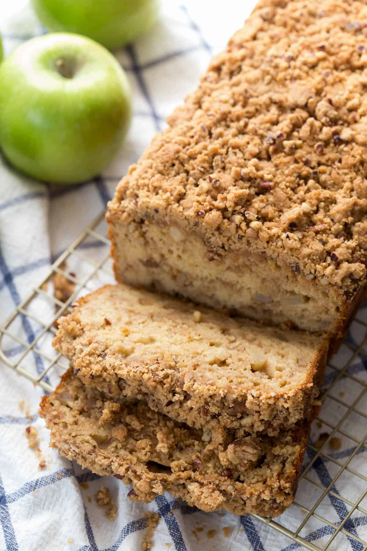 a loaf of apple cinnamon bread with two slices sitting next to it on a baking rack