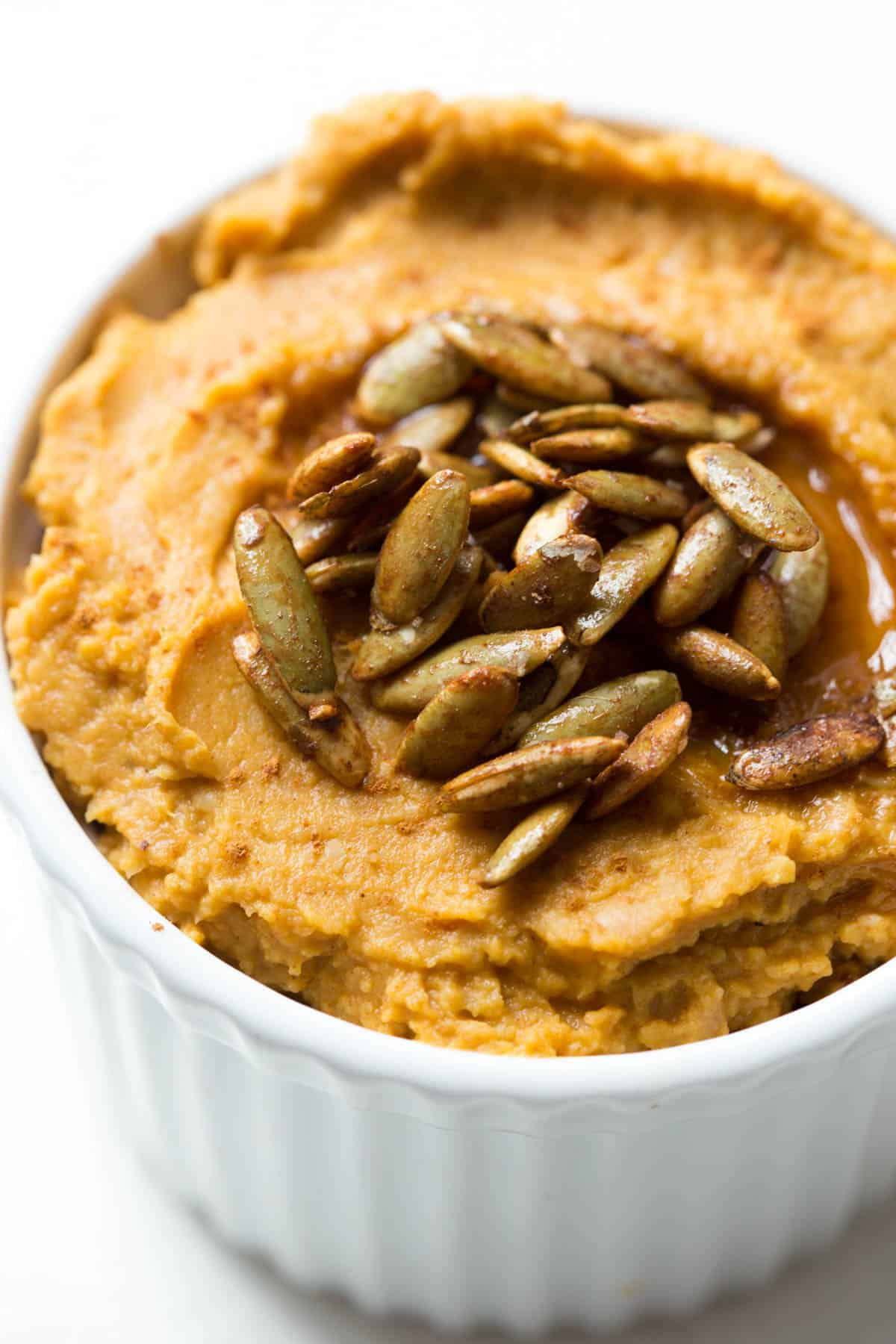 a white bowl filled with pumpkin hummus and topped with pepitas