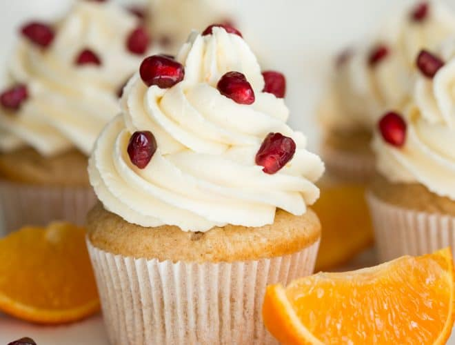 Orange Pomegranate Cupcakes are made with the freshest flavors of the season! The cupcakes are stuffed with a pomegranate spread and topped with orange vanilla buttercream frosting.