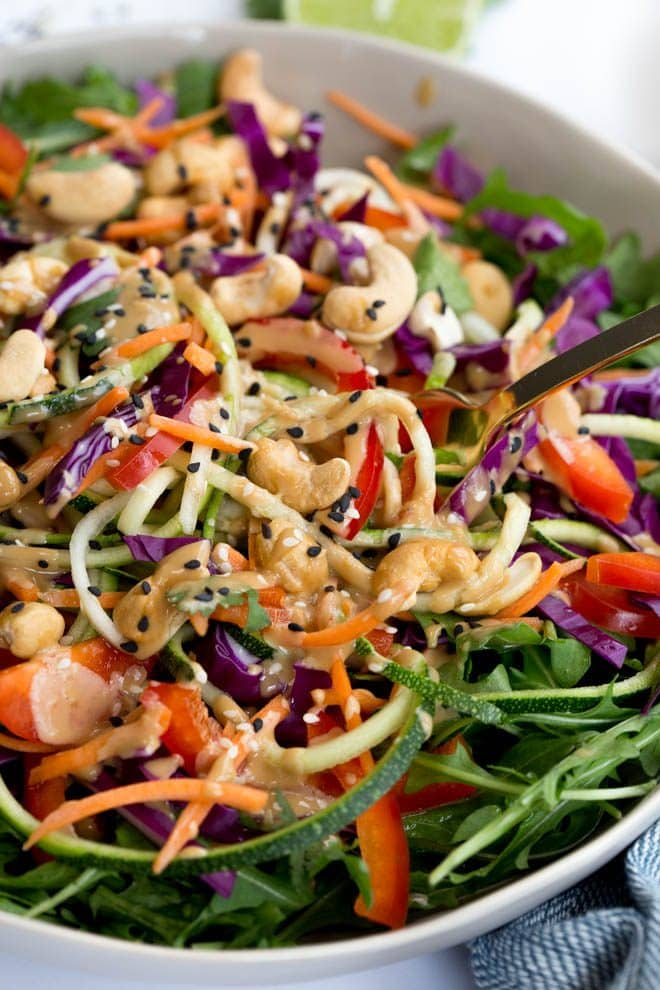 Zucchini Noodle Pad Thai Salad is made with the freshest, raw ingredients including carrots, zucchini, cabbage, arugula, red peppers and a creamy sesame-cashew dressing! #salad #healthy #recipe #raw #cashew #vegan #thai
