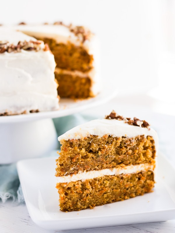 Classic Carrot Layer Cake with Cream Cheese Frosting is moist, flavorful and garnished with chopped pecans. This recipe is a must for Easter or any spring celebration! #carrot #cake #recipe #dessert #cakerecipe #carrotcake #classic #layercake #Easter #Easterrecipe #spring