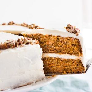 a slice of two layer carrot cake being pulled out from the cake