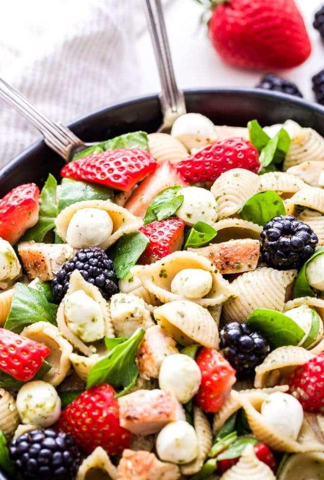This Chicken and Berry Pesto Pasta Salad is a flavorful and easy to make main dish salad. All the flavors of caprese salad, but using berries instead of tomatoes! #pastasalad #pesto #strawberries #chicken