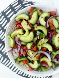 sliced cucumbers, red peppers and red onions in a white bowl sitting on a white background with a blue napkin
