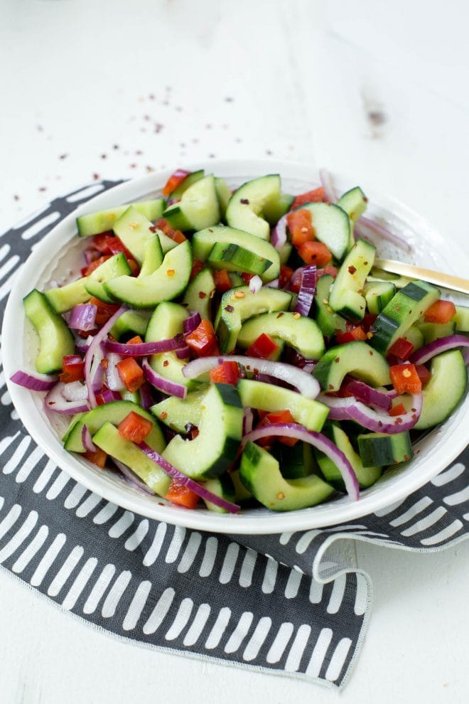 Thai Cucumber Salad is made with a few ingredients and comes together in less than 10 minutes! The salad combines the freshest cucumbers, red onions and bell peppers with a simple and refreshing vinaigrette. #healthy #salad #recipe #cucumber