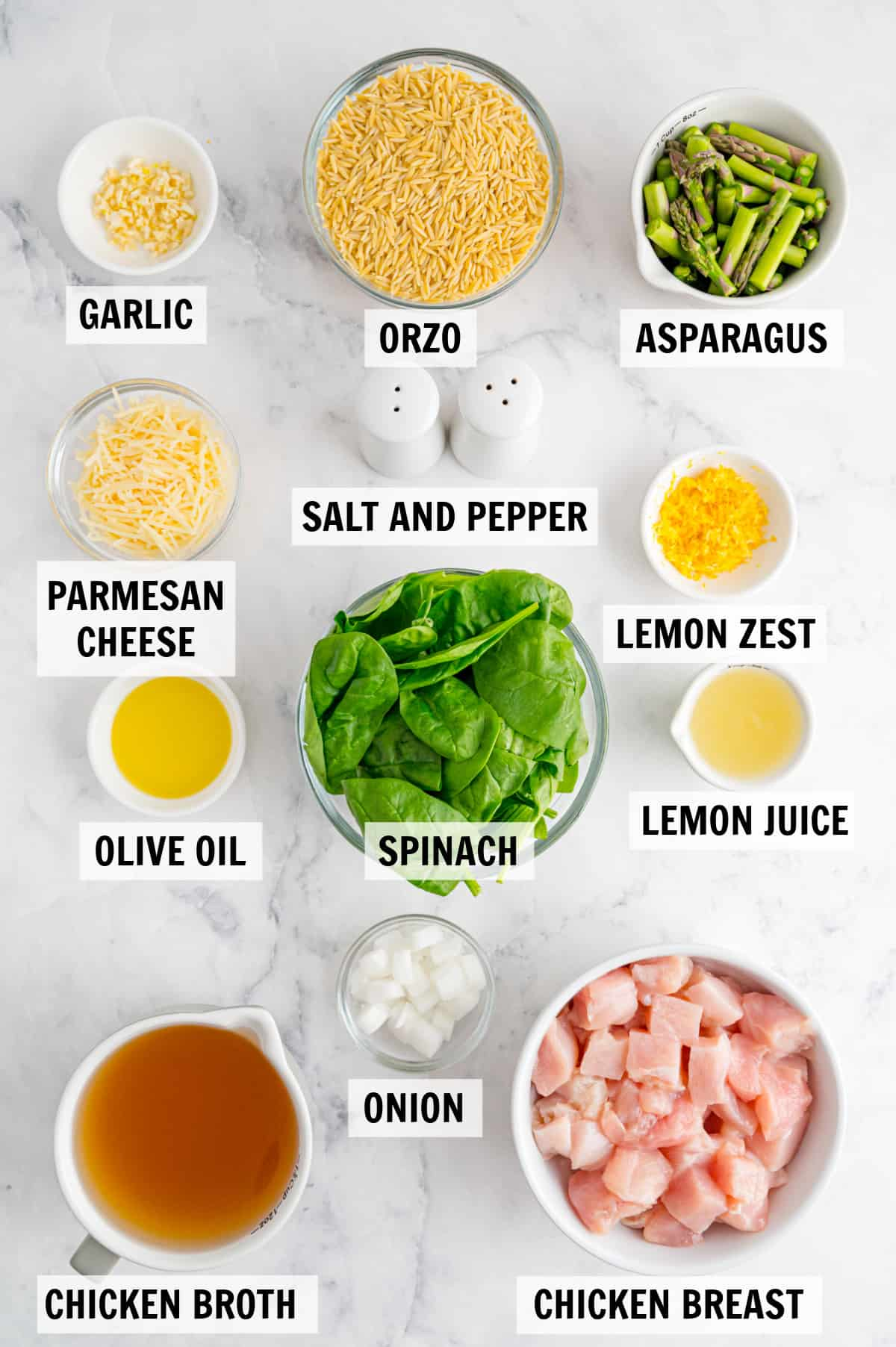 all of the ingredients for lemon orzo with chicken on a white countertop