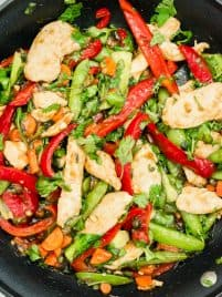cooked chicken teriyaki stir fry garnished with cilantro sitting in a black nonstick skillet