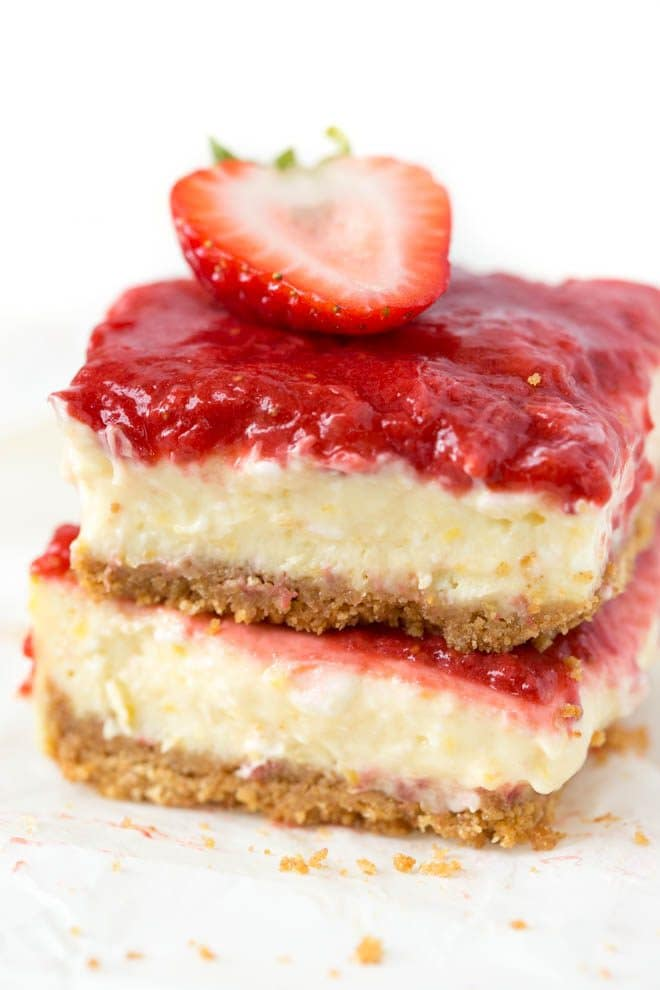 Mango Strawberry Cheesecake Bars are an irresistible treat made with ripe mango, strawberries, cream cheese, sour cream and a few other simple ingredients. They are the perfect summer dessert and combine a light and creamy mango cheesecake with strawberry topping! #mango #cheesecake #strawberry #bars #dessert #recipe