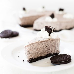 One slice of oreo cheesecake on a white plate.