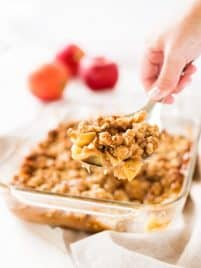 Scoop of apple crisp with a large baking dish of the apple crisp.