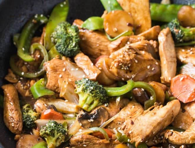 Garlic Sesame Chicken Stir Fry is an easy meal that's on the table in 30 minutes or less and boasts an authentic Chinese stir-fry flavor! Skip take out to make this healthier stir fry at home. #sesame #chicken #stirfry #dinner #recipe #skillet