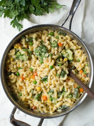 A large pan of veggie mac and cheese with a spoon in it.