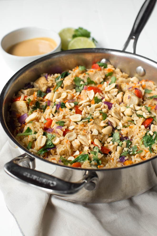 Thai Chicken Peanut Rice Skillet is an easy one pot meal that cooks in less than 30 minutes! It's packed with red bell peppers, carrots, cabbage, baby bok choy, chicken, rice and a creamy peanut sauce. #chicken #peanut #skillet #dinner #weeknight #meal #onepot