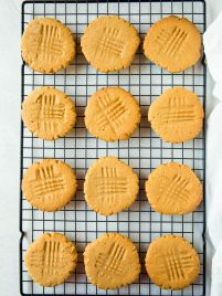 one dozen peanut butter cookies sitting on a cooling rack on a white countertop