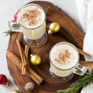 two glass of eggnog with a pinch of nutmeg on top sitting on a wooden background