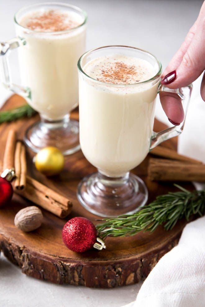 two glasses of homemade eggnog sitting on a wooden serving tray