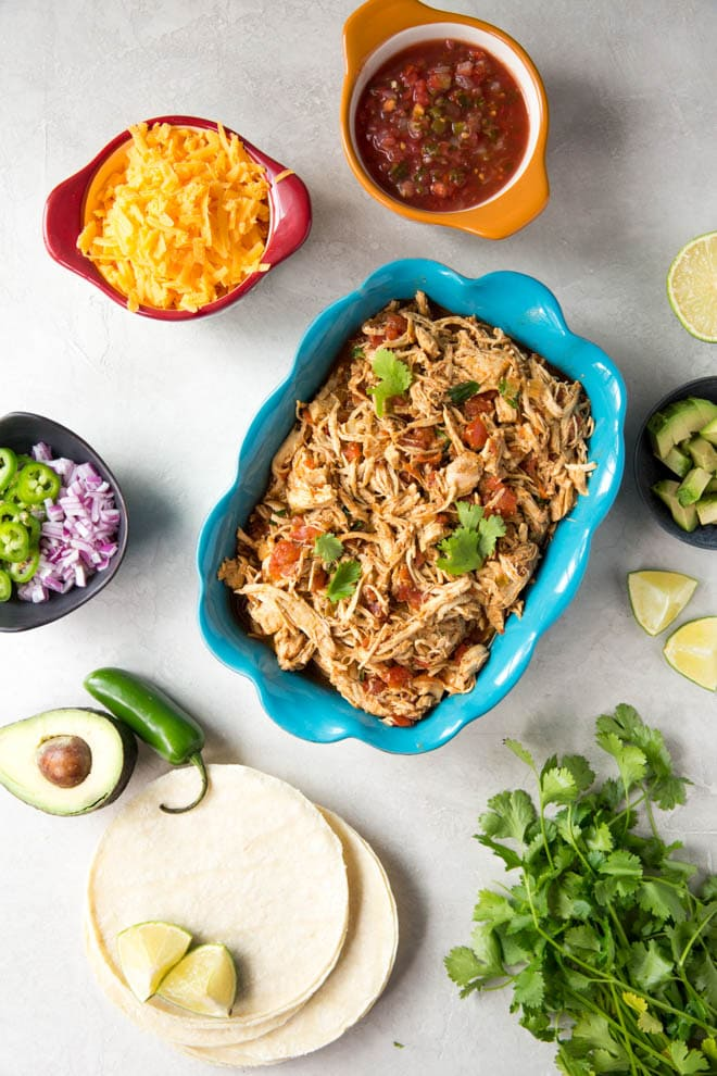 Easy Shredded Chicken Tacos recipe cooks in the slow cooker or crockpot. It's made with only a few ingredients that you probably already have in your pantry. #slowcooker #crockpot #chicken #tacos #recipe #dinner