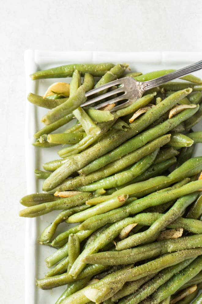 Cook fresh green beans in a skillet with garlic to make this simple garlic green beans recipe! #garlic #greenbeans #recipe #dinner #sidedish #vegetarian #healthy #recipe