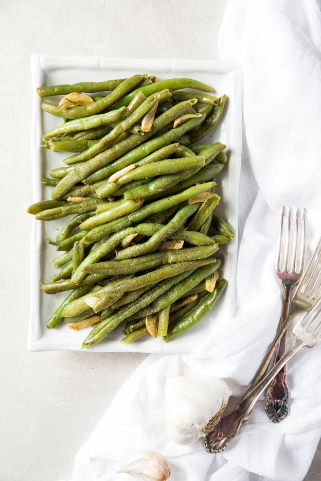 Follow this simple recipe for how to cook fresh green beans to make these Garlic Green Beans! The green beans cook in one skillet in less than 15 minutes. #healthy #dinner #greenbeans #fresh #sidedish #farmersmarket #csa #vegetables
