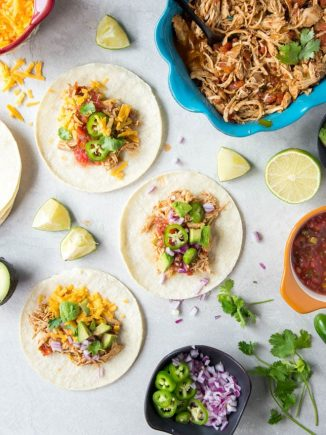 Slow Cooker Shredded Chicken Tacos are made with only a few ingredients and cook in your crockpot. It's the perfect meal for any day of the week! #slowcooker #chicken #tacos #recipe #weeknight #meal #dinner #crockpot