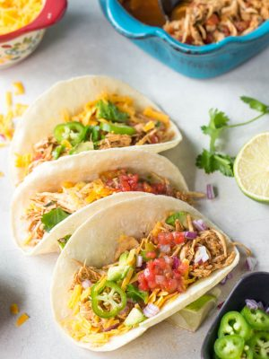 Easy shredded chicken tacos made in the slow cooker or crockpot with only a few ingredients! Create a dinner the entire family will love. #family #dinner #chicken #tacos #recipe #healthy