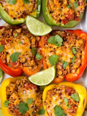 Six stuffed peppers sitting in a White dish with slices of lime and fresh parsley on top.