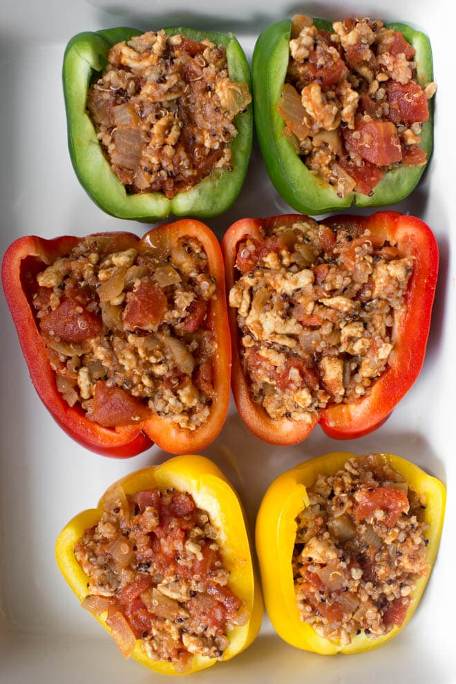 Three peppers stuffed with turkey quinoa filling in a white rectangle dish are ready to go into the oven.