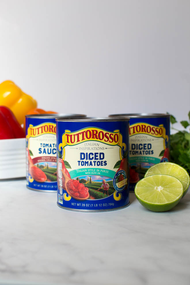 Three cans of Tuttorosso tomatoes Italian Style sitting on a white table with a slice lemon and parsley on the right side and a bowl full of peppers sitting on the left.
