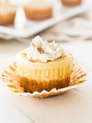 One mini carrot cake cheesecake on a white background.