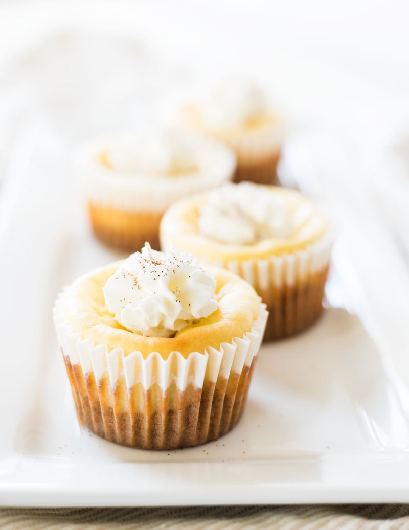 Four mini carrot cake cheesecakes sitting on a rectangle plate.