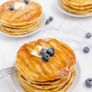 three stacks of blueberry buttermilk pancakes sitting on white plates on a counter