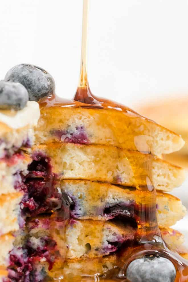 a cut pieces of blueberry buttermilk pancakes with maple syrup on top