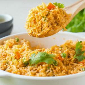A wooden spoon takes a scoop of cauliflower rice out of a round white serving dish.