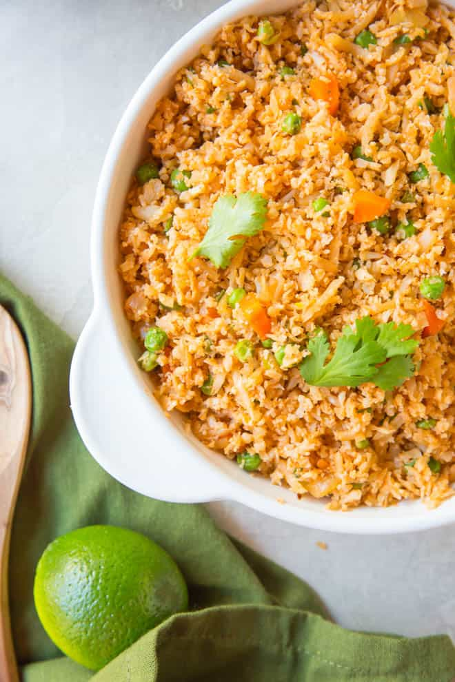 A large bowl of Mexican cauliflower rice sitting on a table next to a green napkin and a lime.