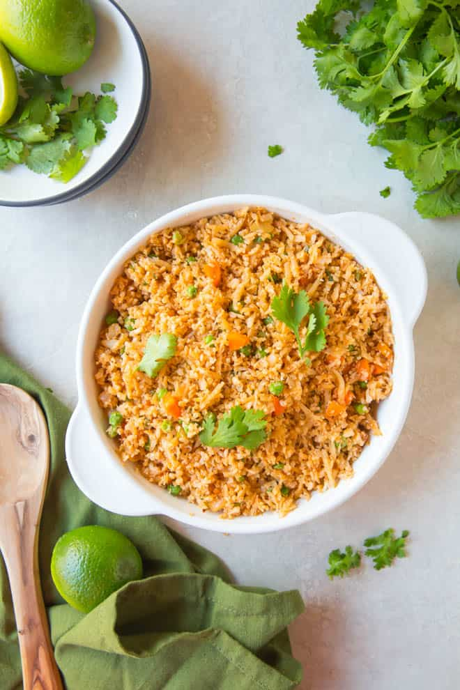A large bowl of Mexican cauliflower rice sitting on a white table with a green napkin and wooden spoon off to the side.
