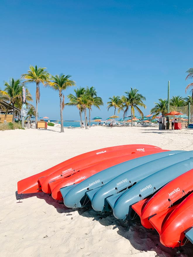 Blue and red kayaks on the beach with palm trees in the background.
