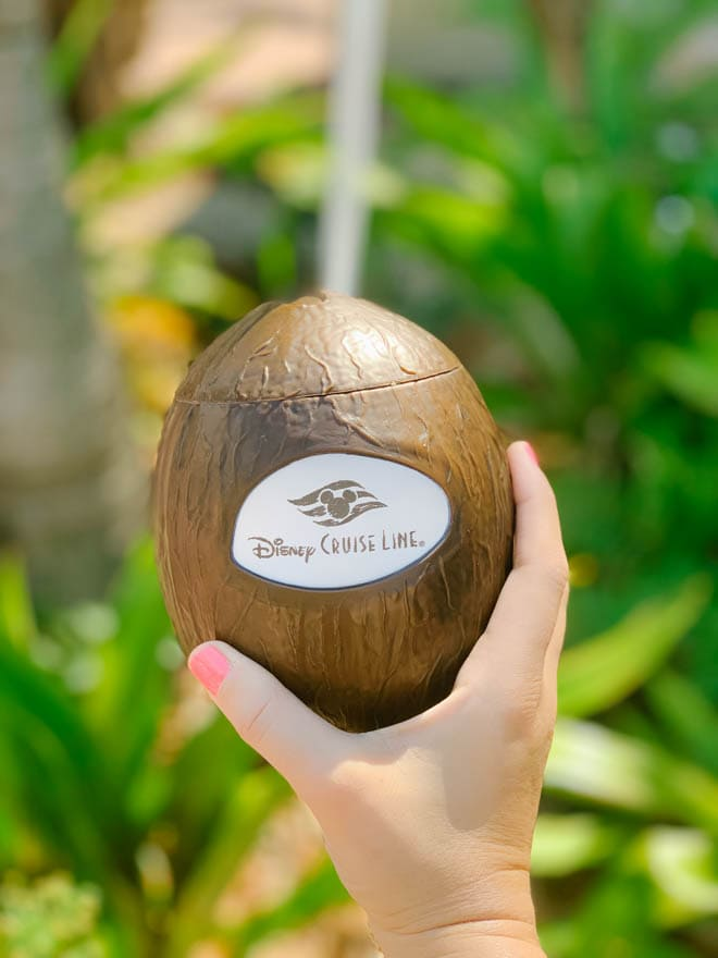 Holding a coconut cup in one hand that says Disney Cruise Line.
