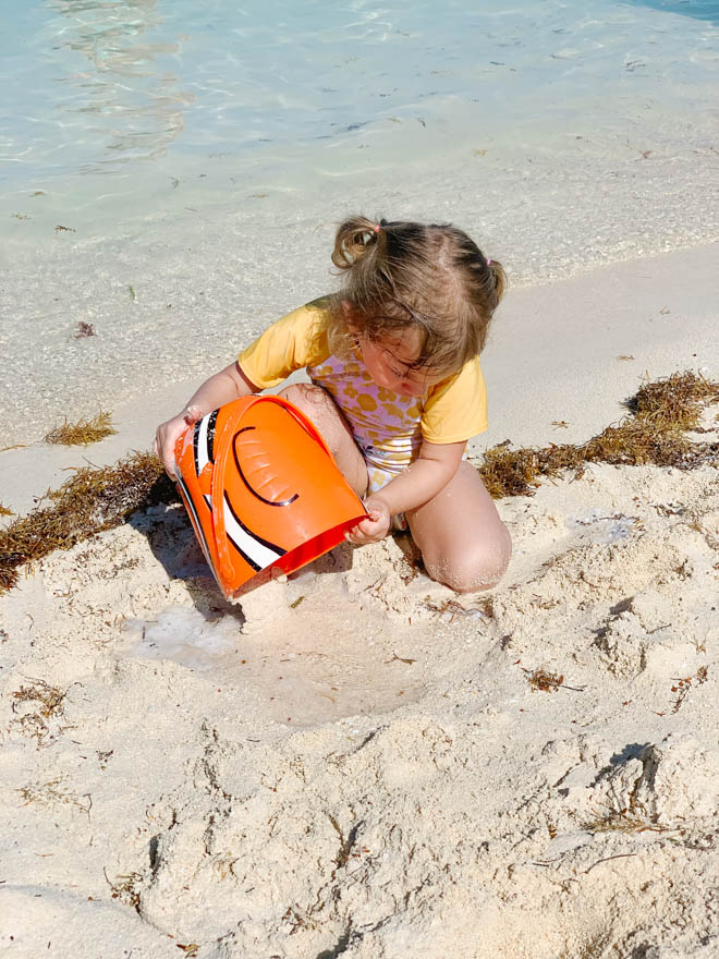 A toddler building a sandcastle in the sand at Castaway Cay beach.