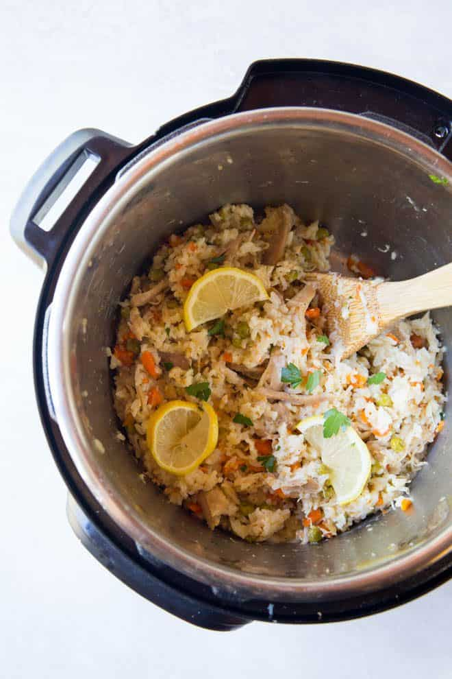 Cooked chicken and rice is sitting in the instant pot. A wooden spoon is scooping the rice.