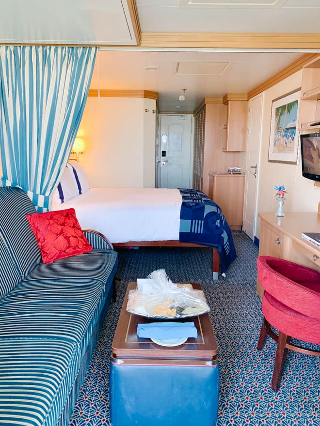 cruise ship cabin room with bed, couch and chair.