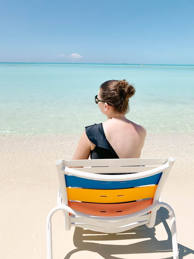 woman sitting in a chair on the beach in the bahamas with calm clear water.