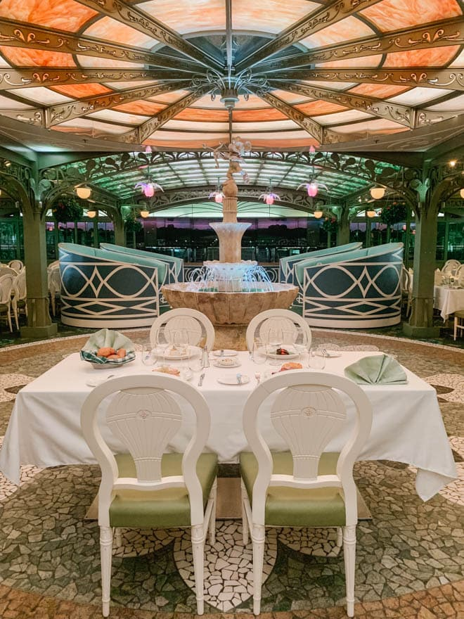 Enchanted garden on the Disney Dream table setting with fountain in the background.
