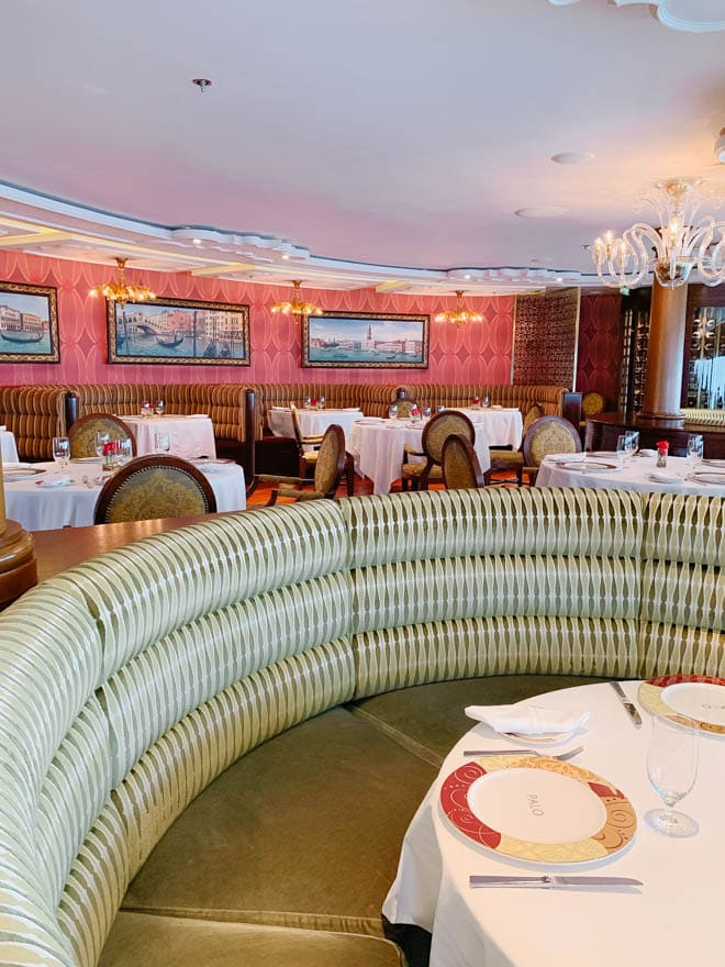 An elegant Italian inspired restaurant on a Disney cruise ship with tables and chairs and white tablecloths.