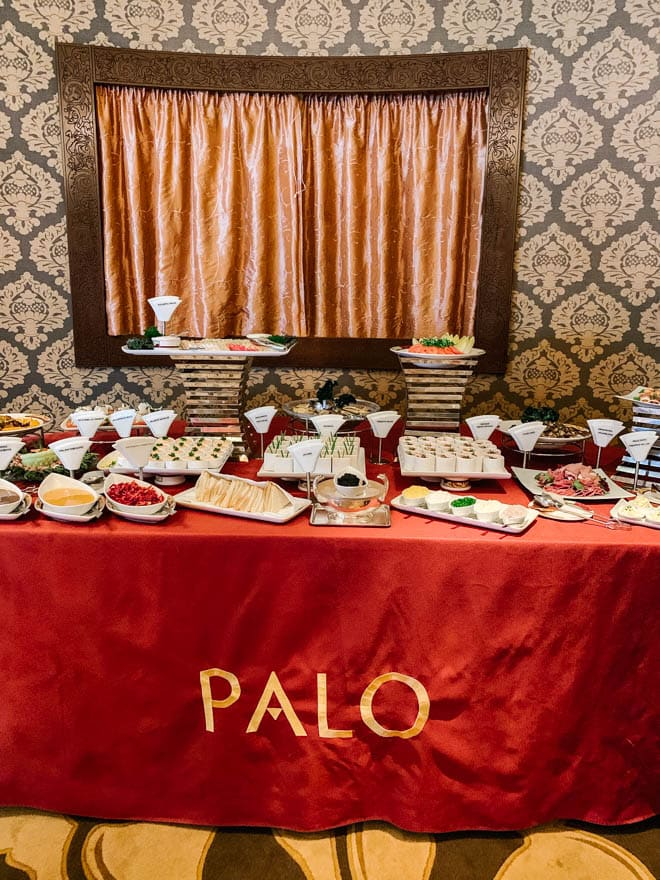 A table with a red tablecloth filled with an assortment of brunch dishes.