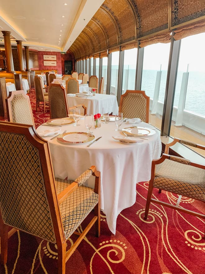 An elegant dining room at Palo restaurant Disney Cruise with white tablecloths overlooking the sea.