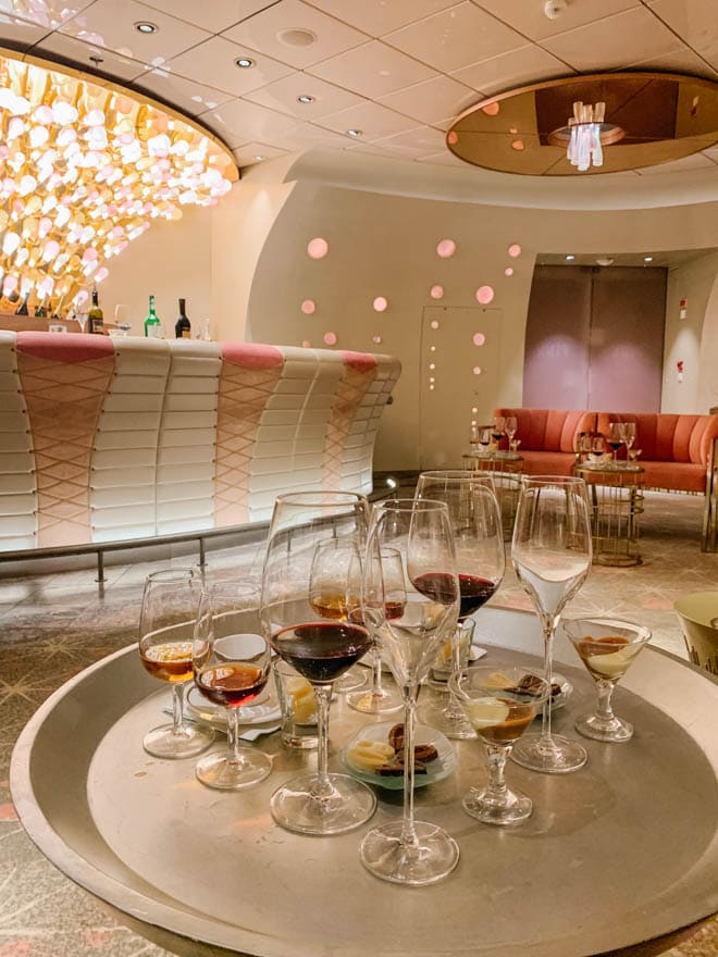 Glass of wine and liquor with chocolate set on a table in a pink lounge.