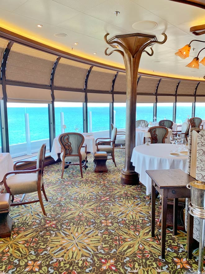 Photo os the Remy dining room on the Disney Cruise with tables and chairs overlooking the ocean.